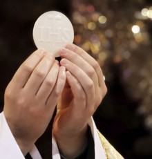 Priest holding up the eucharist